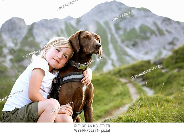 Austria, South Tyrol, young girl with her dog