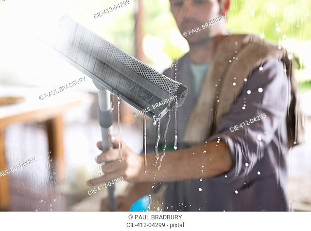 Man washing window with squeegee