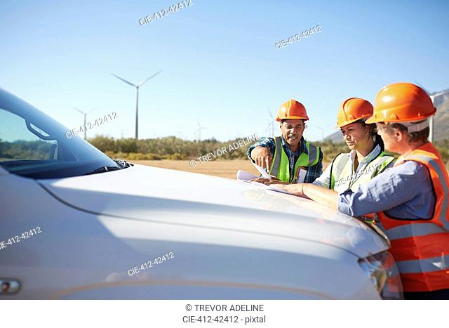 Engineers reviewing blueprint on truck at sunny wind turbine power plant