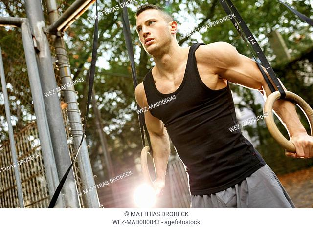 Muscly young man training on gymnastic rings