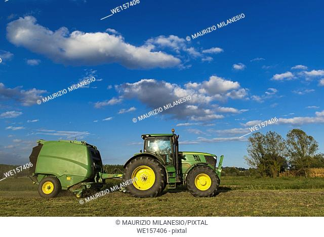 Piedmont, Italy, Tractor with machinery to make bales of hay, trees bottom and cloudy blue sky
