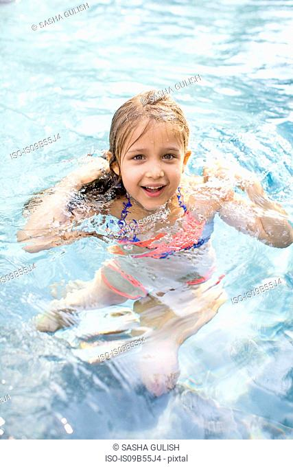 Portrait of girl treading water in outdoor swimming pool