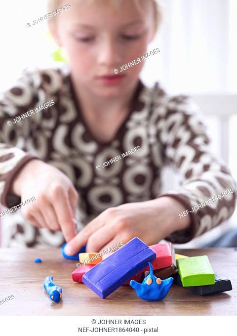 Boy playing plasticine