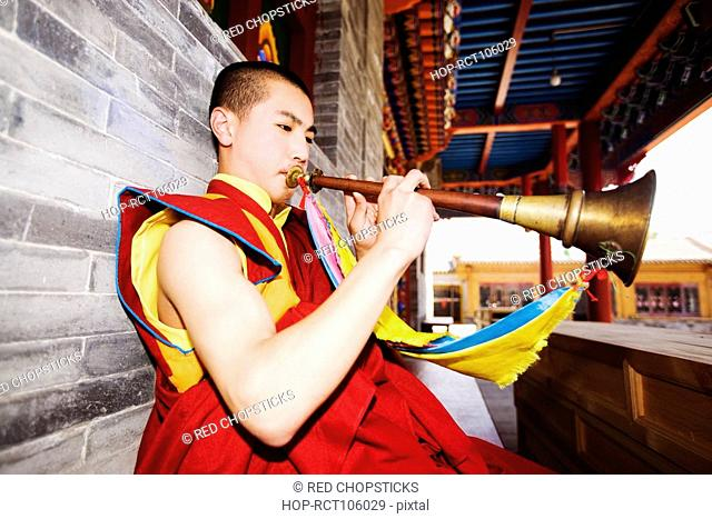 Young man playing horn in a temple, Da Zhao Temple, Hohhot, Inner Mongolia, China