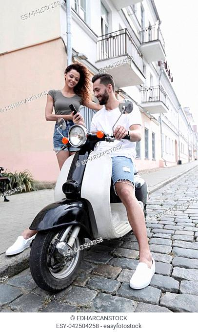 Stylish young couple sits a scooter in the street
