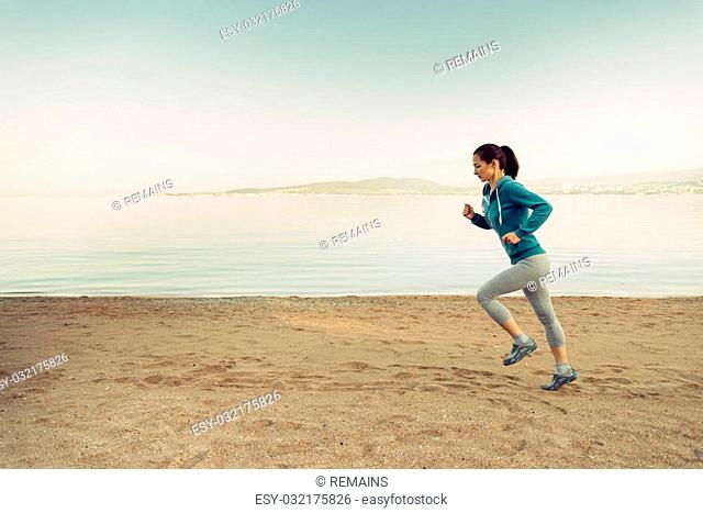 Young woman running on sand beach near the sea in summer in the morning. Concept of sport and healthy lifestyle. Space for text in the left part of image