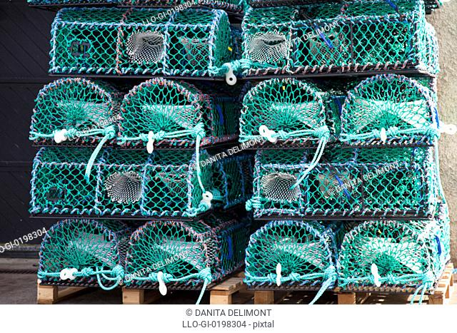 New crab, prawn or lobster pots, stacked on dock near marina, Anstruther, Fife Council Area, Scotland, UK