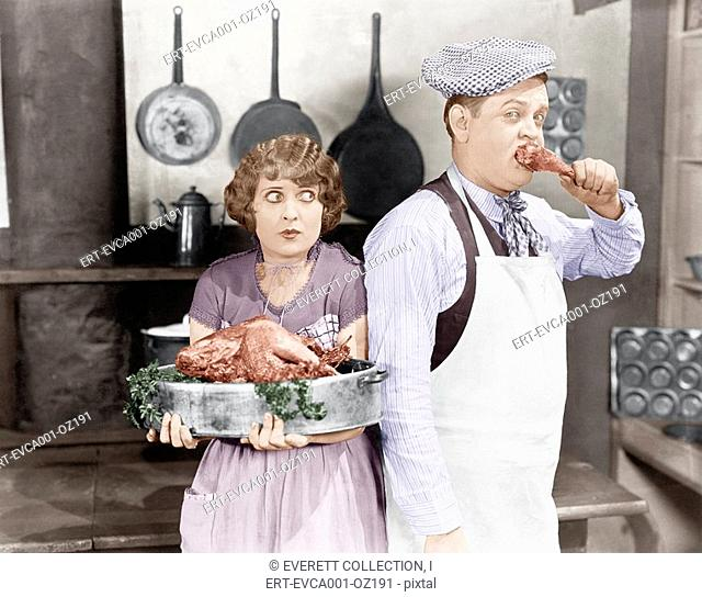 Couple standing together in a kitchen with a cooked turkey Old Visuals