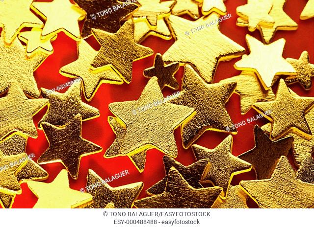 Christmas golden decoration with gold star over red background
