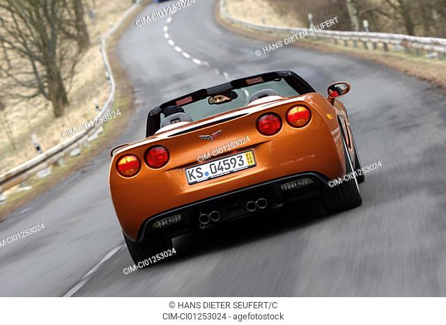 Corvette C6, rust-red model year 2008, orange -metallic, driving, diagonal from the back, rear view, country road, open top