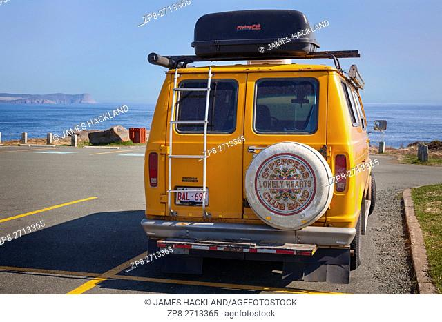 A Ford Econoline 150 van in a parking lot overlooking the Atlantic Ocean with a Sgt Peppers tire cover on the back. Cape Spear, Newfoundland, Canada