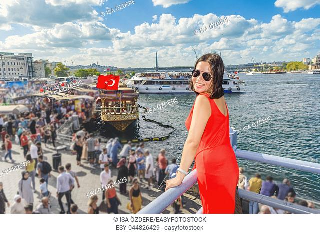 Beautiful Chinese woman poses over Galata Bridge with view of crowd in Eminonu district