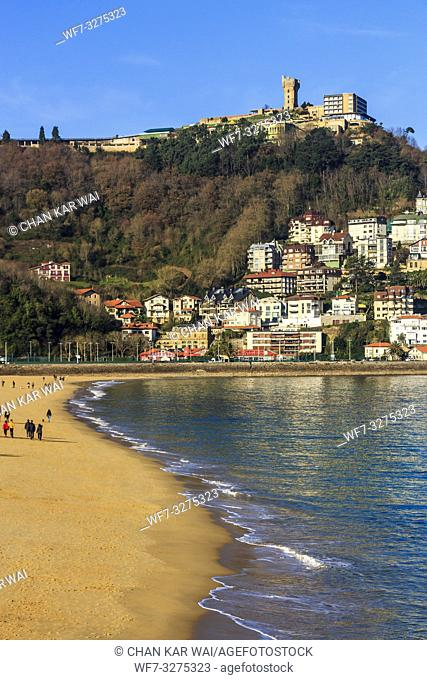 San Sebastian, Spain - Jan 2019: Ondarreta beach and in the distance houses and apartments on Igeldo mountain range