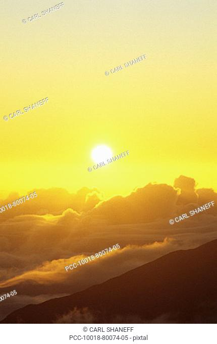 Sunball above cloudy mountaintop in yellow sunset sky