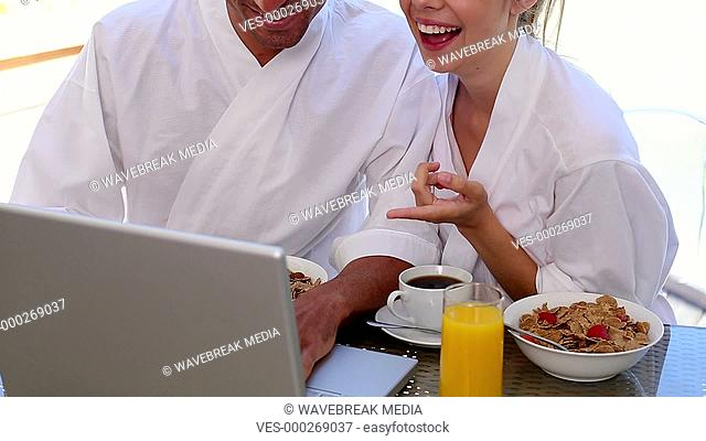Happy couple having breakfast together looking at laptop