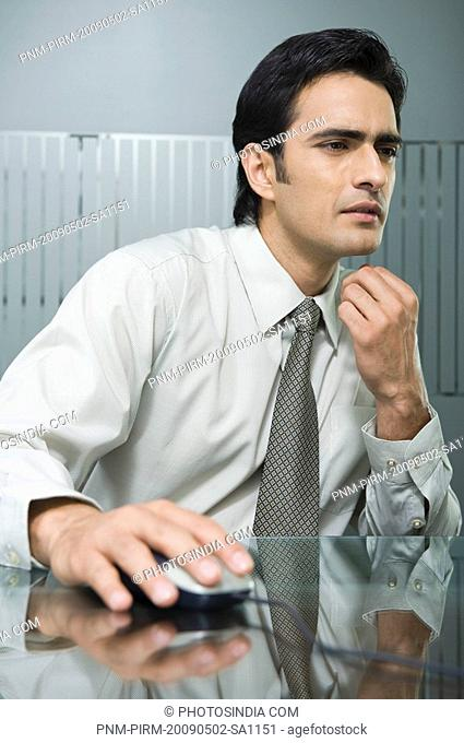 Businessman operating a computer mouse in an office