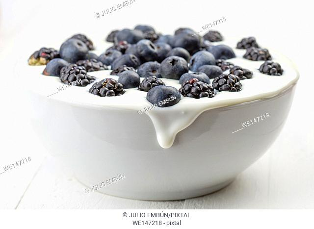 flooded breakfast bowl of yogurt and berries on white wooden