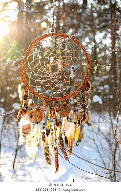 Handmade colorfull dream catcher in the snowy forest. Tribal elements, owl feathers