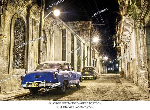 Vintage cars parked in the street at night  Ciudad de La Habana, Cuba, Caribbean