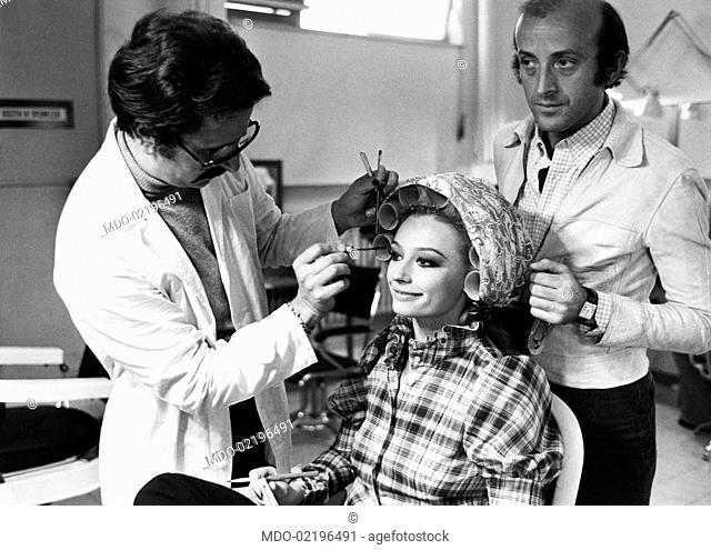 Make-up artist of the TV programme Canzonissima Enzo Amato applying mascara to dancer and presenter Raffaella Carrà before the beginning of the TV show