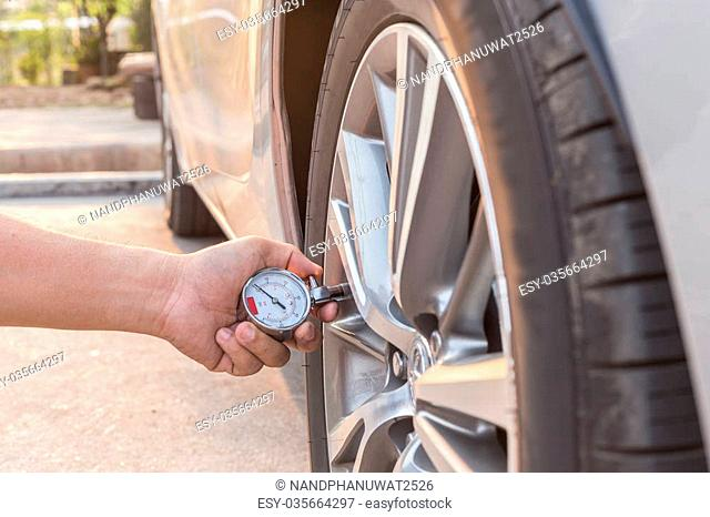 Man holding pressure gauge and checking air pressure of his car