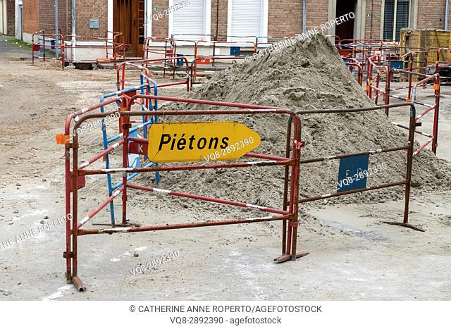 Masonry sand heap with pedestrian walk way barrier in the old quarter of medieval Berques, France