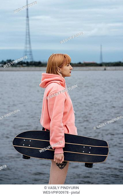 Young woman holding carver skateboard standing at the riverside