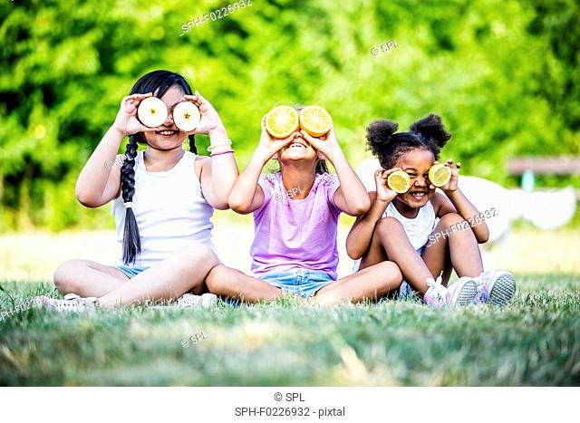 Girls sitting and holding various fruits