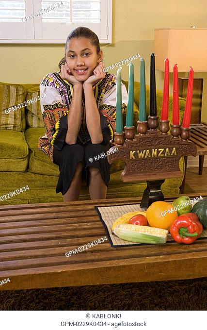 Portrait of happy African American pre-adolescent girl celebrating Kwanzaa in living room indoors, looking at camera