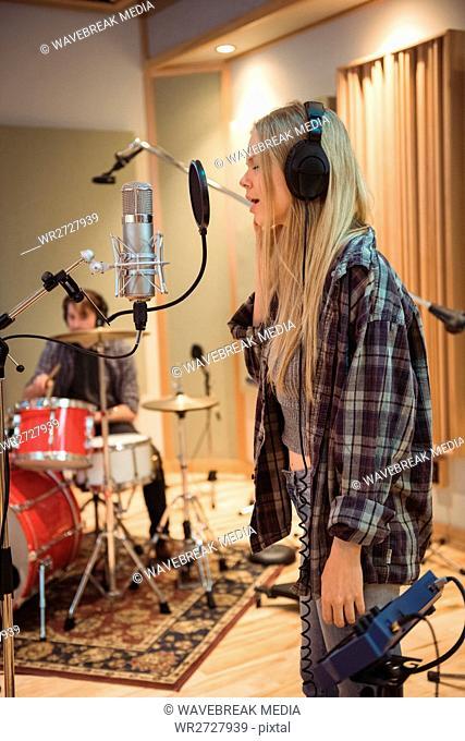 Woman singing in recording studio