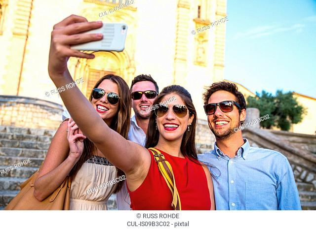 Two tourist couples in sunglasses taking selfie in front of church, Calvia, Majorca, Spain