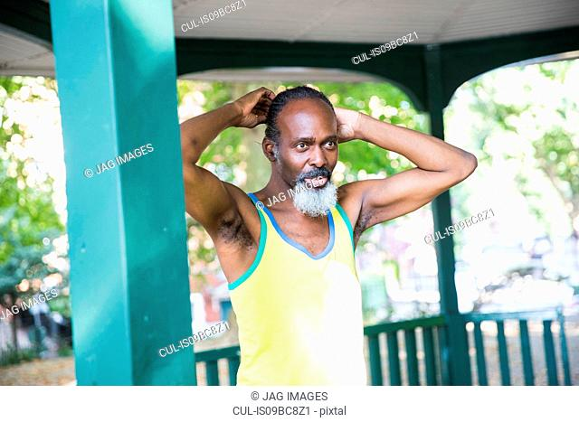 Mature man standing under bandstand, pensive expression
