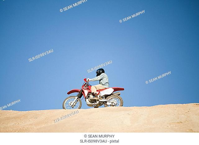 Man riding dirt bike on hill