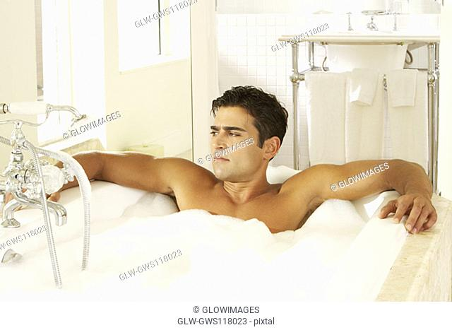 High angle view of a bare chested young man in a bubble bath