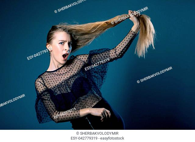 closeup portret of young beautiful woman in amazement trying to raise his hair on blue grey background. emotions. model test