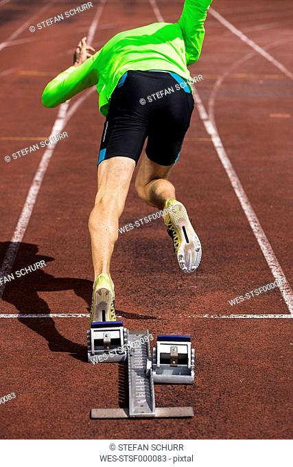 Germany, Young man running from sprint start
