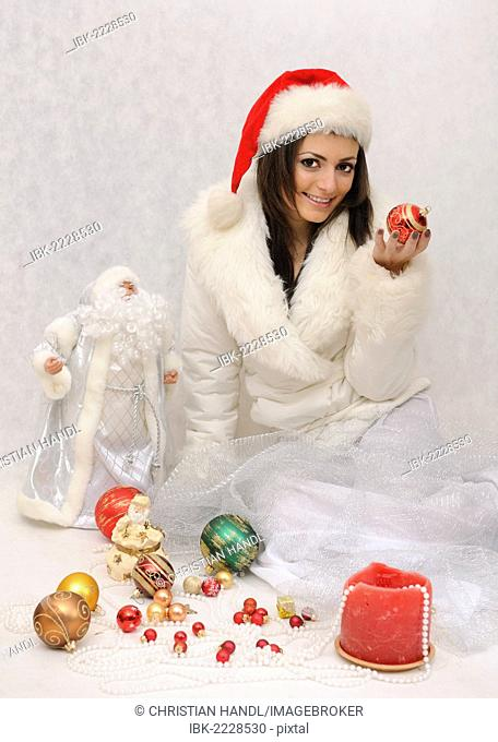 Young woman with Santa hat and a white faux fur jacket surrounded by Christmas decorations