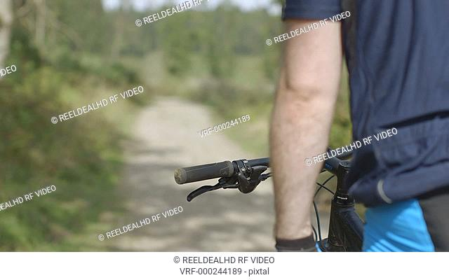 Man cycling through uneven forest track