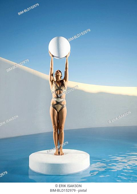 Caucasian woman holding sphere on ice floe
