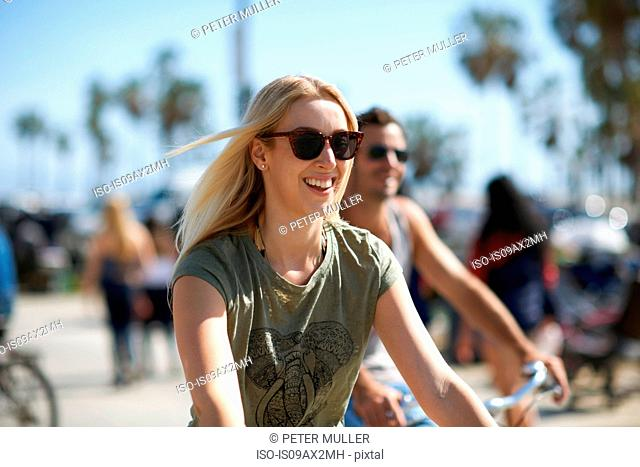 Young woman and boyfriend cycling at Venice Beach, Los Angeles, California, USA