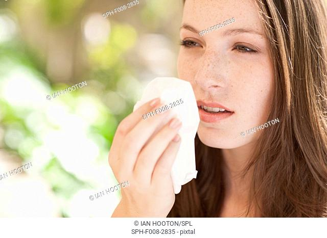 MODEL RELEASED. Young woman sneezing