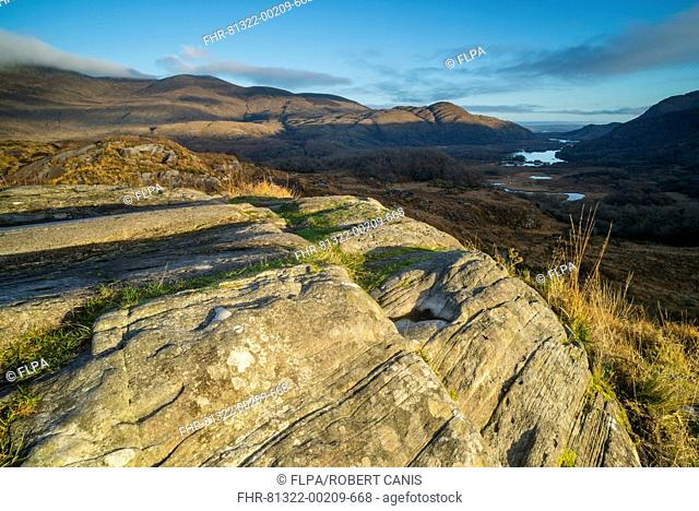View over rocks on moorland towards lake and mountains at dawn, Ladies View, Lough Leane (Lower Lake), Lakes of Killarney, Killarney N.P