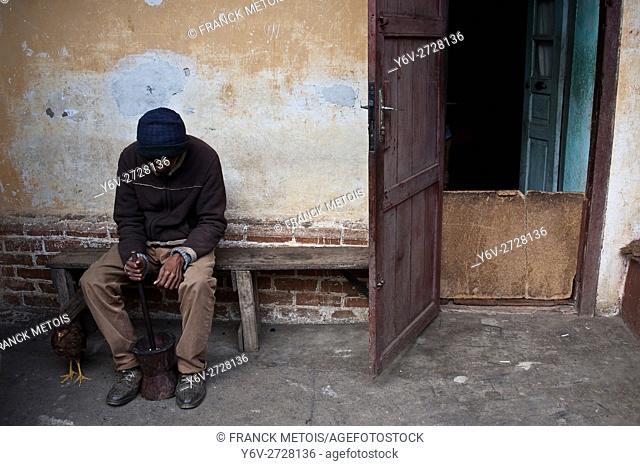 Old man crushing peanuts in front of his house. At Fianarantsoa upper city ( Madagascar)