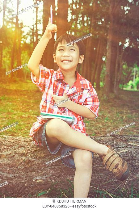 Happy asian boy can resolve problem at park. Outdoors in the day time with bright sunlight. Children planning and education concept
