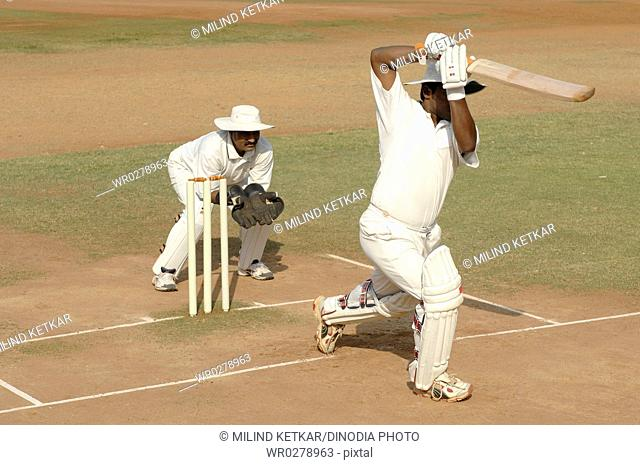 Indian left handed batsman in action playing straight drive shot in cricket match MR705I