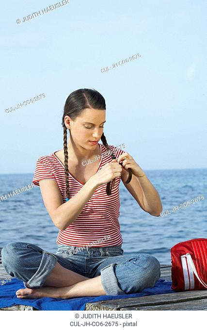 Young girl sitting on jetty plaiting herself pigtails