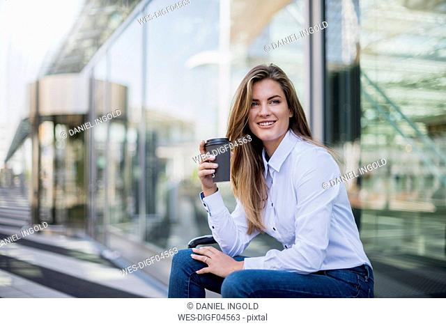 Portrait of smiling young businesswoman with coffee to go