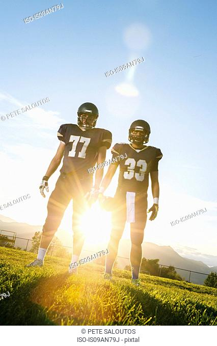 Portrait of two teenage american football players at sunset