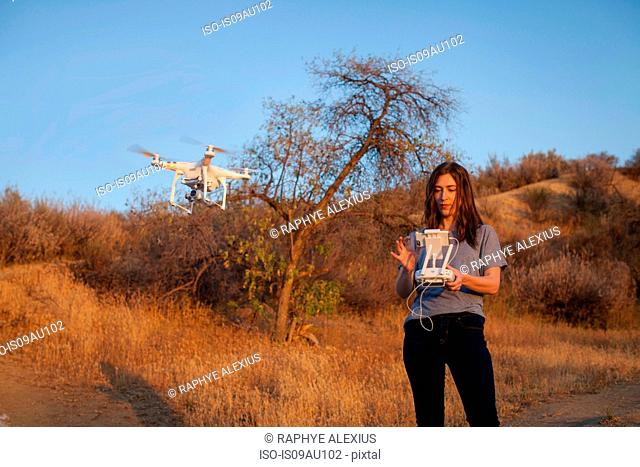Female commercial operator on scrubland flying drone, looking down, Santa Clarita, California, USA