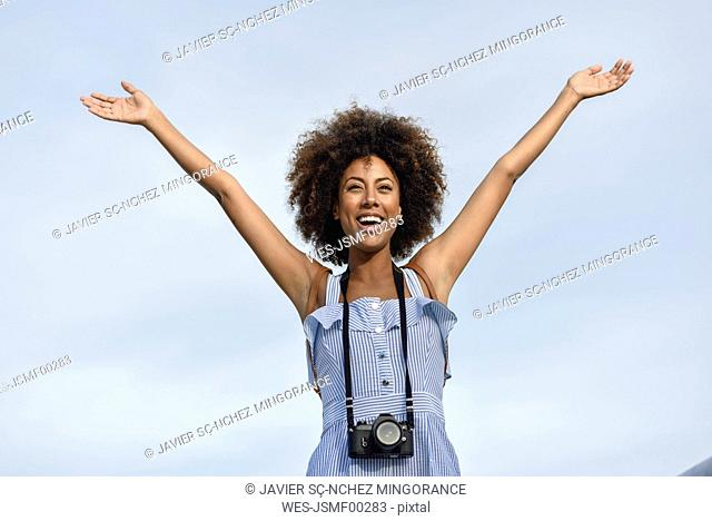 Portrait of happy young woman with camera against sky